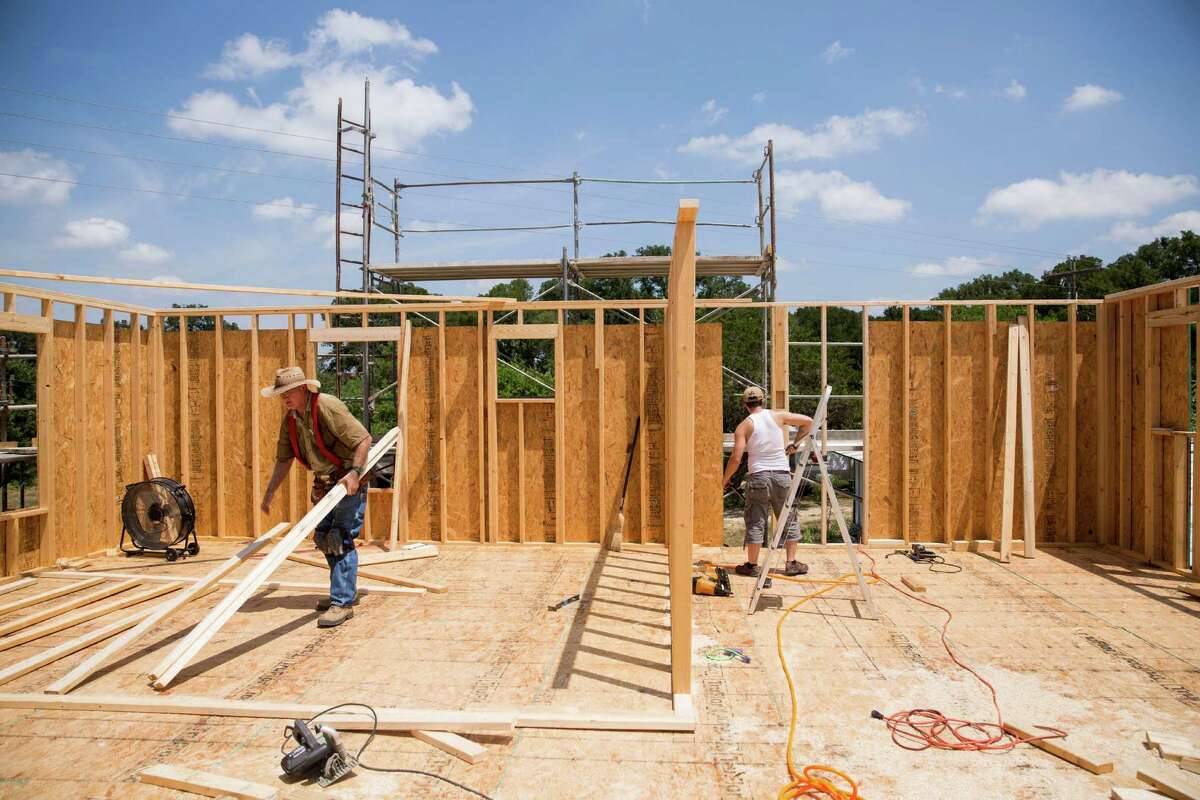 Mike Rieken and Jarrell Bamberger work on the Bamberger family's new home in Blanco, Texas on August 18, 2015. The Bambergers are rebuilding after losing their home and belongings in the Memorial Day floods.