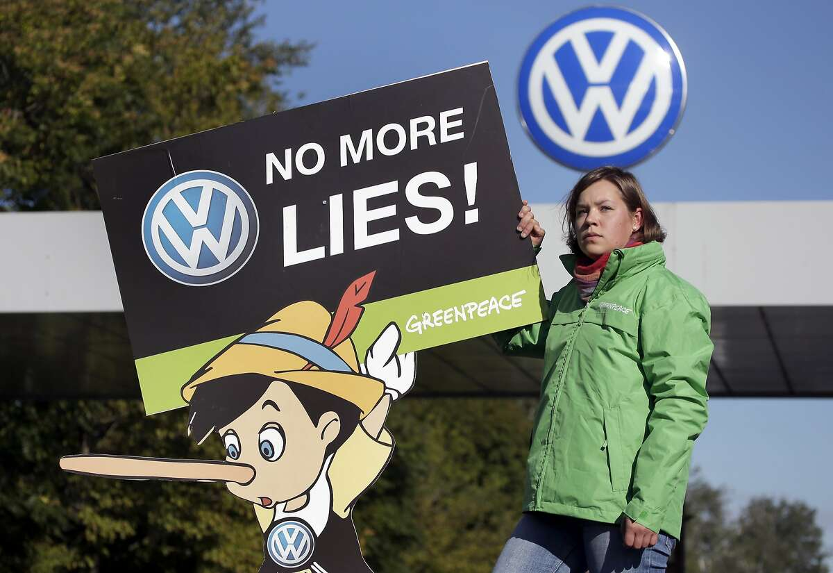 An activist of the environmental protection organization 'Greenpeace' holds a protest poster in front of a factory gate of the German car manufacturer Volkswagen in Wolfsburg, Germany, Friday, Sept. 25, 2015, where the supervisory board meet to discuss who to name as CEO after Martin Winterkorn quit the job this week over an emissions-rigging scandal that's rocking the world's top-selling automaker. (AP Photo/Michael Sohn)