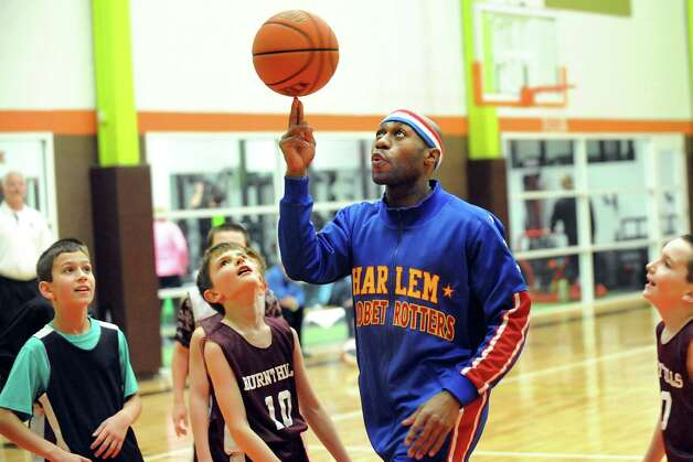 """Harlem Globetrotters Tay """"Firefly"""" Fisher, center, spins the ball on a finger as he plays with the Burnt Hills 4th-grade travel basketball team on Thursday, Jan. 29, 2015, at Vent Fitness in Guilderland, N.Y. Fisher and the Globetrotters will bring their game to the Times Union Center on Sunday at 1 p.m. (Cindy Schultz / Times Union) Photo: Cindy Schultz / 00030375A"""