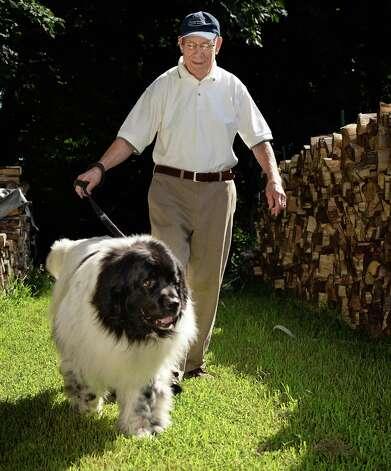 Orin Sussman walks his therapy dog Elmo, a 7-yr.-old Newfoundland Black & White, through his yard Friday August 7, 2015 in Colonie, NY.  (John Carl D'Annibale / Times Union) Photo: John Carl D'Annibale / 10032869A