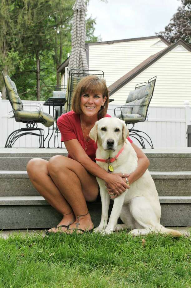 Ann Halburian poses with her dog, Oasis, at her home on Thursday, Aug. 27, 2015, in Albany, N.Y.  Oasis who is six years old, first lived with Halburian when Oasis was eight weeks old and in the Guiding Eyes for the Blind program to become a seeing eye dog.  Oasis did not work out as a seeing eye dog and so Halburian was able to adopt her.  Oasis now is used as a therapy dog.  (Paul Buckowski / Times Union) Photo: PAUL BUCKOWSKI / 00033084A