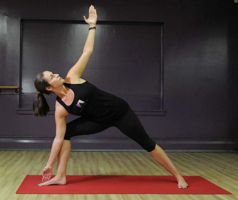 Yoga instructor Jessica Lustig does the Triangle representing Bikram Yoga on Tuesday, Aug. 25, 2015, at The Hot Spot Yoga in Latham, N.Y. (Cindy Schultz / Times Union) Photo: Cindy Schultz / 00033087A