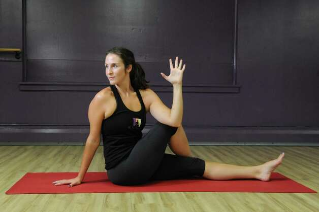 Yoga instructor Jessica Lustig does the Seated Spinal Twist representing Jivamukti Yoga on Tuesday, Aug. 25, 2015, at The Hot Spot Yoga in Latham, N.Y. (Cindy Schultz / Times Union) Photo: Cindy Schultz / 00033087A