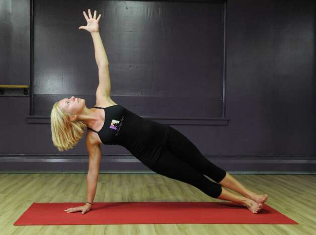 Yoga instructor Kayla Tote does the Side Plank representing Baptiste Yoga on Tuesday, Aug. 25, 2015, at The Hot Spot Yoga in Latham, N.Y. (Cindy Schultz / Times Union) Photo: Cindy Schultz / 00033087A