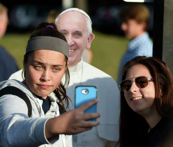 Willow Carey, 17, left, make a selfy with her friend Olivia Danise, 17 and a cardboard cut of Pope Francis before boarding a bus Friday morning Sept. 25, 2015 in Albany, N.Y.,  to New York City to see the Pope at Madison Square Garden this evening.  (Skip Dickstein/Times Union) Photo: SKIP DICKSTEIN / 10033481A