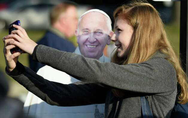 A woman makes a selfie with a cardboard cutout of Pope Francis before boarding a bus Friday morning Sept. 25, 2015 in Albany, N.Y.,  to New York City to see the Pope at Madison Square Garden this evening.  (Skip Dickstein/Times Union) Photo: SKIP DICKSTEIN / 10033481A