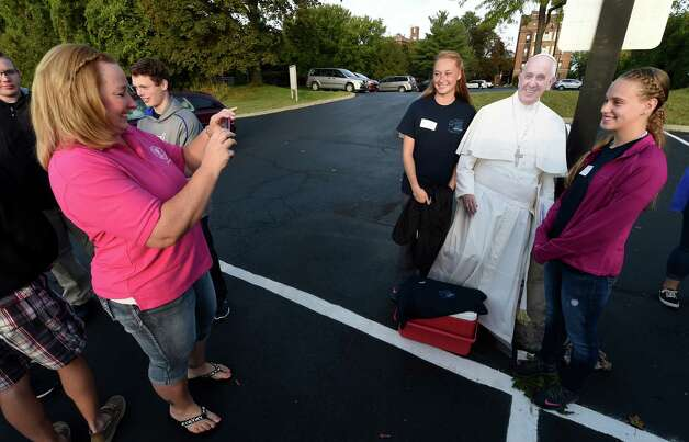 Jennifer Mohoney, left makes a photo of Aleyah Proper,16, left and Kat Rice, 15, and a cardboard cut of Pope Francis before boarding a bus Friday morning Sept. 25, 2015 in Albany, N.Y.,  to New York City to see the Pope at Madison Square Garden this evening.  (Skip Dickstein/Times Union) Photo: SKIP DICKSTEIN / 10033481A