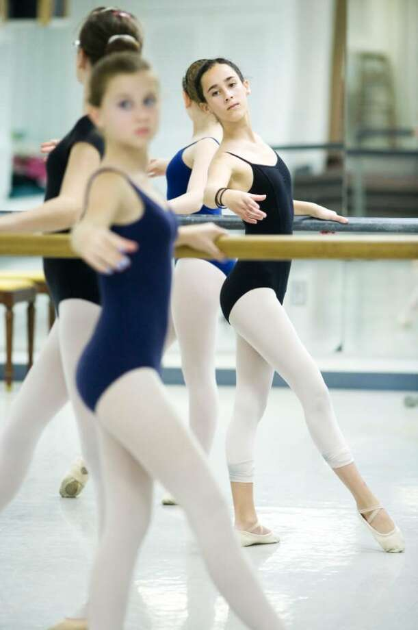 Maddie Hohmeister, 12, right, and Abigail Mitchell, 13, front, practice the barre exercises with other students during a class at The Ballet School of Stamford on Broad Street on Mar. 19, 2010. The school is negotiating a lease deal with the City of Stamford to move into the basement of the Old Town Hall building. Photo: Kerry Sherck / Stamford Advocate