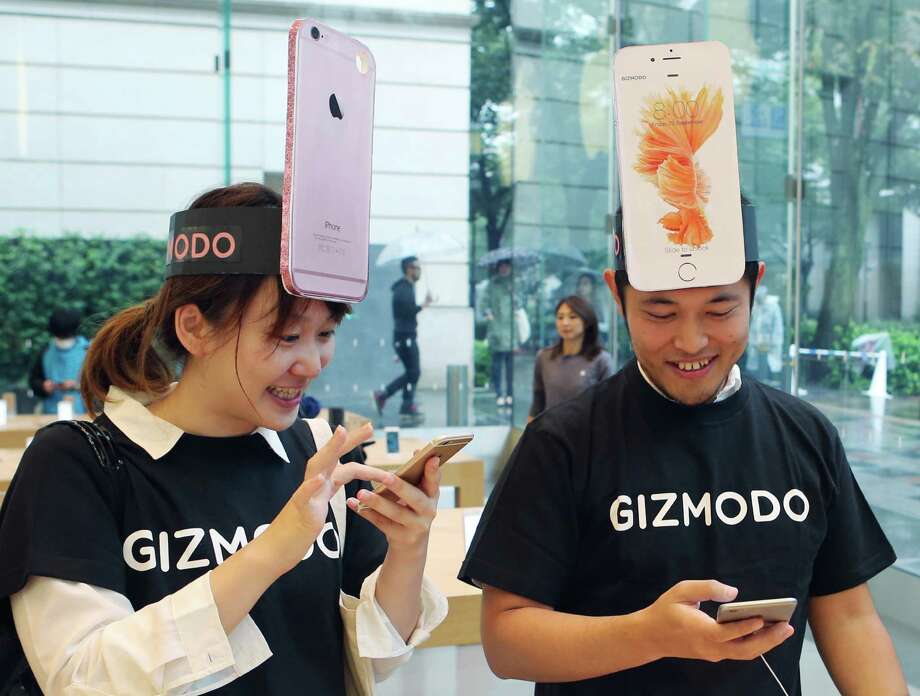 Customers Makiko Maeda, left, and Naoki Tsukamoto react Friday after they purchased new iPhone 6s in Tokyo. Apple is counting on sales of the new iPhones to maintain its top-ranked global position. Photo: Koji Sasahara, STF / AP