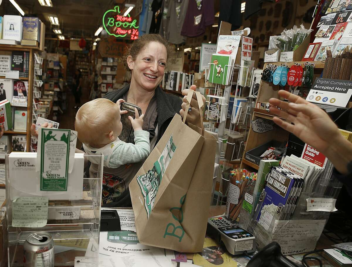Rose Martin grabs her bag after using her chip card to process a purchase at Green Apple Books in San Francisco, Calif., on Thursday, September 24, 2015. Martin mentioned noticing the use of chip cards in Europe ten years ago.