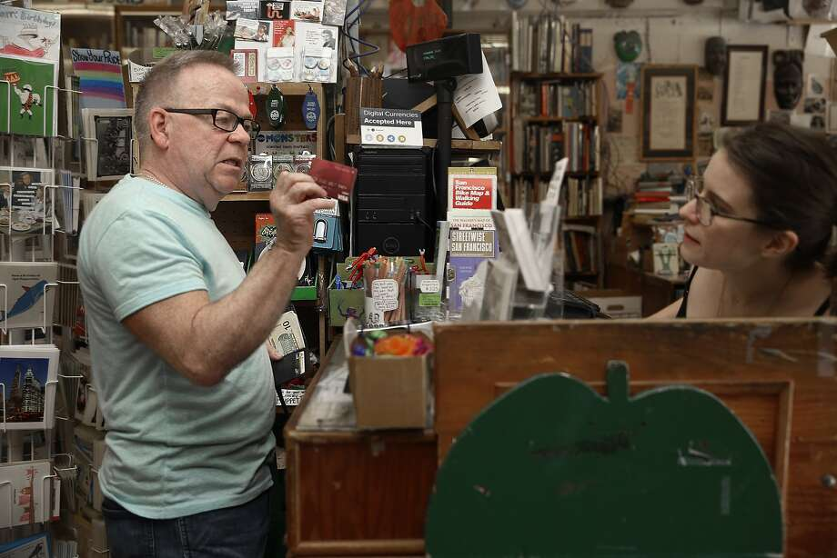 Will Seng (left) asks manager Eden Mackey (right) if his card has a chip at Green Apple Books in San Francisco, Calif., on Thursday, September 24, 2015. Photo: Liz Hafalia, The Chronicle