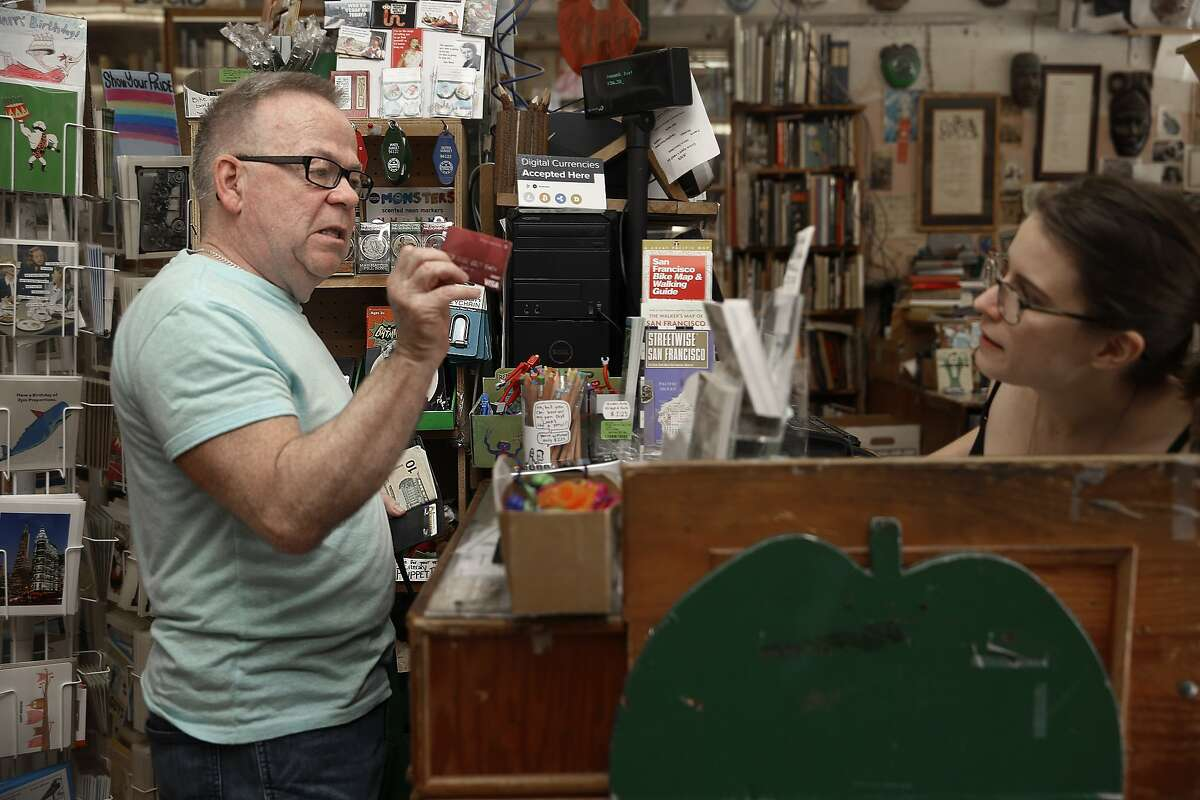 Will Seng (left) asks manager Eden Mackey (right) if his card has a chip at Green Apple Books in San Francisco, Calif., on Thursday, September 24, 2015.