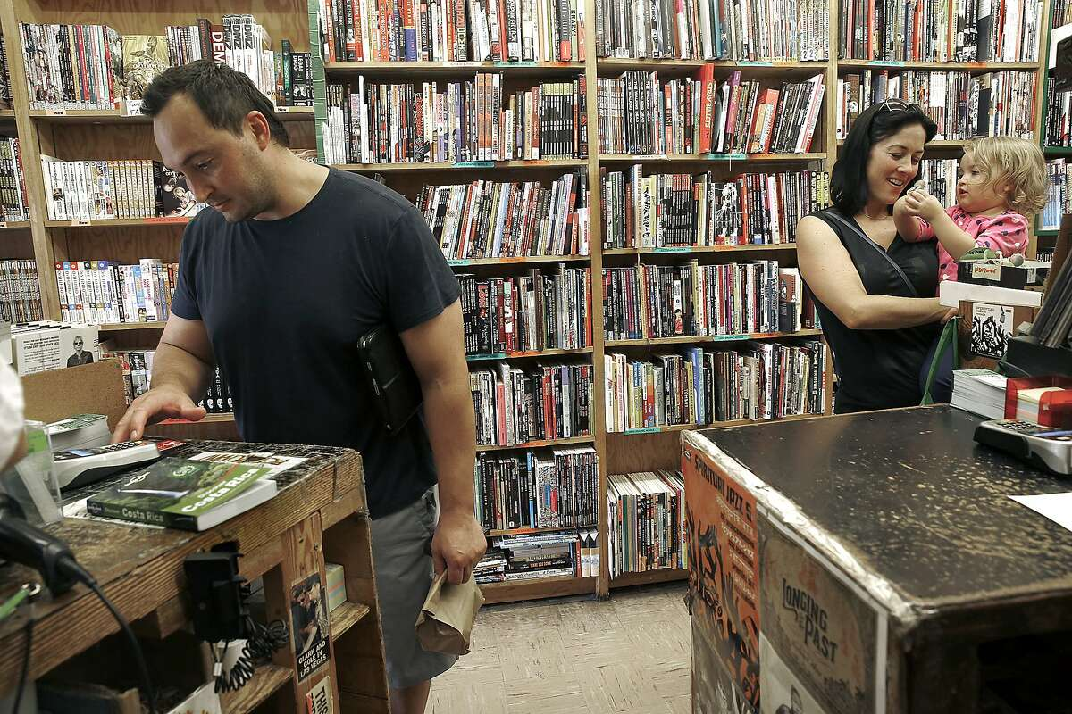 Benny Ramirez (left) makes a purchase with his chip card at Green Apple Books in San Francisco, Calif., on Thursday, September 24, 2015. Ar right is his wife Amy Ramirez and two year old Olivia Ramirez.