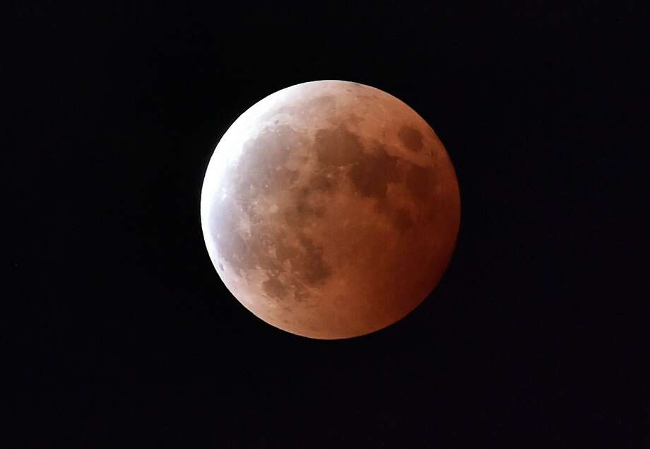 "(FILES) -- This file photo taken on October 8, 2014 shows a lunar eclipse as seen from Tokyo. For the first time in decades, skygazers are in for the double spectacle on September 28, 2015 of a swollen ""supermoon"" bathed in the blood-red light of a total eclipse. AFP PHOTO / Yoshikazu TSUNO  YOSHIKAZU TSUNO/AFP/Getty Images Photo: Yoshikazu Tsuno, AFP / Getty Images"
