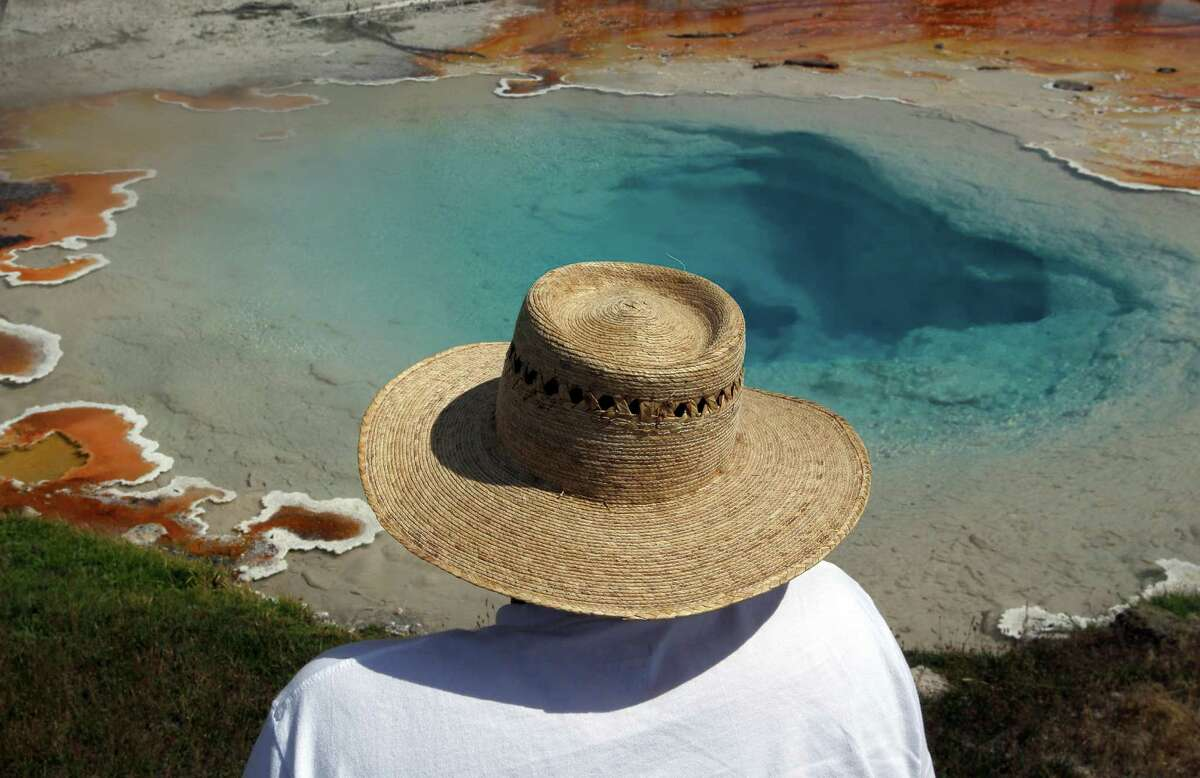 Visitors to the Lower Geyser Basin in Yellowstone National Park are in awe of the amazing colors created by the bacteria and thermophile living in the hot water in Silex Spring on July 21, 2015.