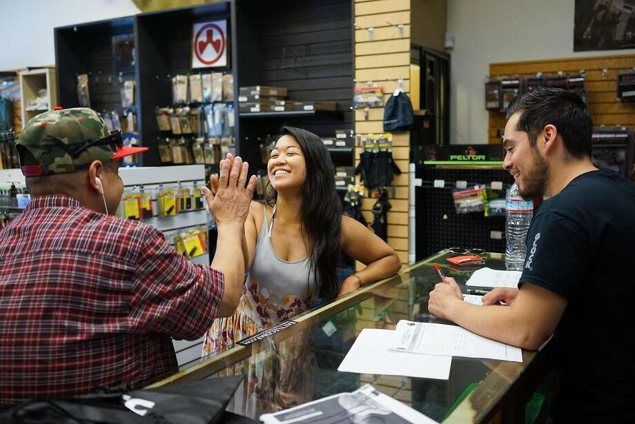 Stephanie Timblin, center, high fives Angel Castro after she passed a test allowing her to buy a firearm at High Bridge Arms in San Francisco, Calif. on Friday, Sept. 25, 2015. The gun shop will be closing next month after a city supervisor required that all gun buys be recorded. Photo: James Tensuan, Special To The Chronicle