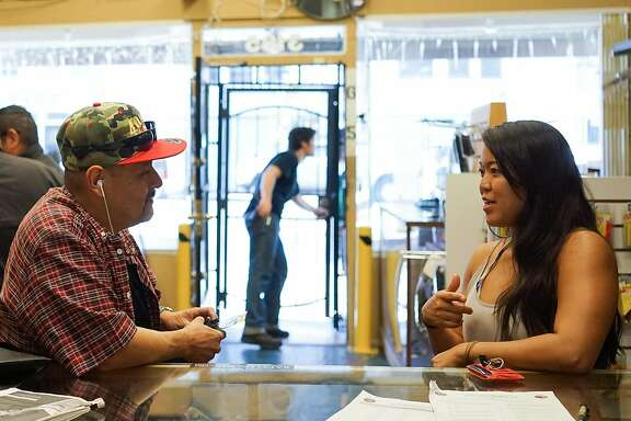 Angel Castro, left, and Stephanie Timblin talk at High Bridge Arms in San Francisco, Calif. on Friday, Sept. 25, 2015. The gun shop will be closing next month after a city supervisor required that all gun buys be recorded.