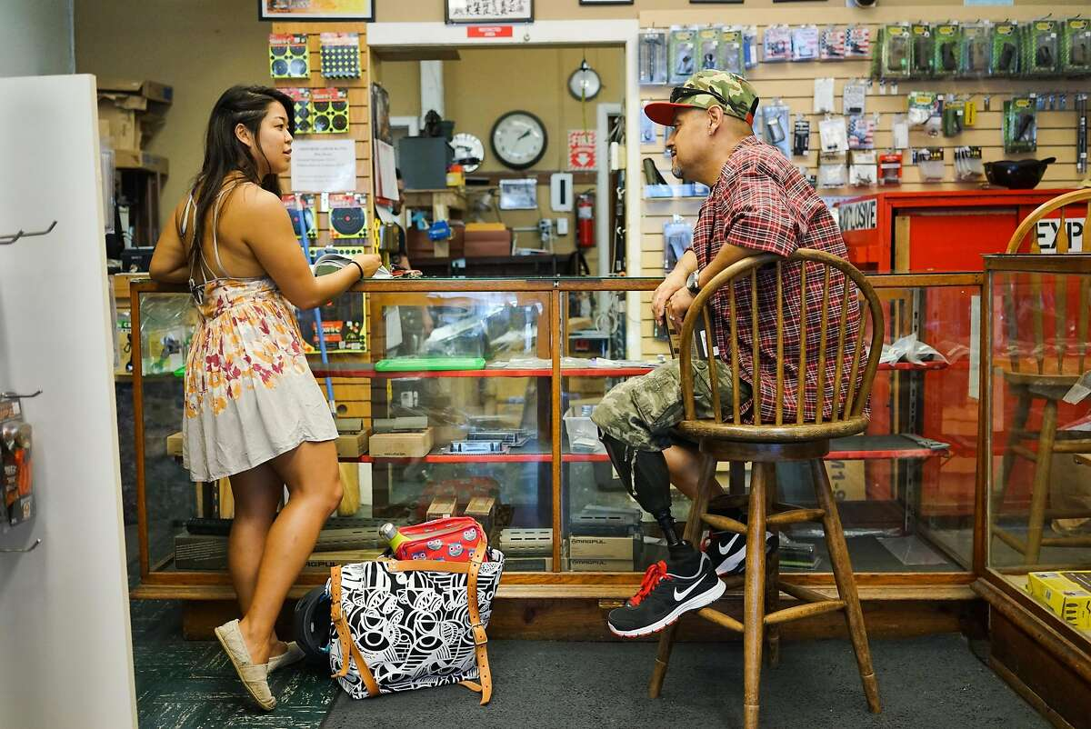 Stephanie Timblin, left, and Angel Castro talk at High Bridge Arms in San Francisco, Calif. on Friday, Sept. 25, 2015. The gun shop will be closing next month after a city supervisor required that all gun buys be recorded.