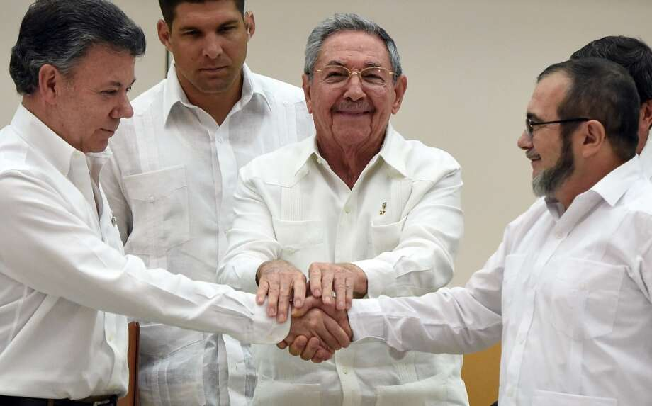 Colombian President Juan Manuel Santos (L) and the head of the FARC guerrilla Timoleon Jimenez (R), shake hands as Cuban President Raul Castro (C) holds their hands during a meeting in Havana on September 23, 2015. Photo: LUIS ACOSTA, AFP / Getty Images