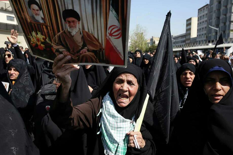 "An Iranian worshipper holds a poster of Iranian Supreme Leader Ayatollah Ali Khamenei, and late revolutionary founder Ayatollah Khomeini, at top left of the poster as she chant slogans while attending an anti-Saudi protest rally on Thursday, after their Friday prayer service in Tehran, Iran, Friday, Sept. 25, 2015. Thousands of Iranian worshippers have marched in Tehran after Friday prayers to denounce the ""incompetency"" of Saudi Arabia in handling the annual hajj pilgrimage. The protest came a day after at least 719 pilgrims died during a crush on the outskirts of the holy city of Mecca. (AP Photo/Vahid Salemi) Photo: Vahid Salemi, STR / AP"