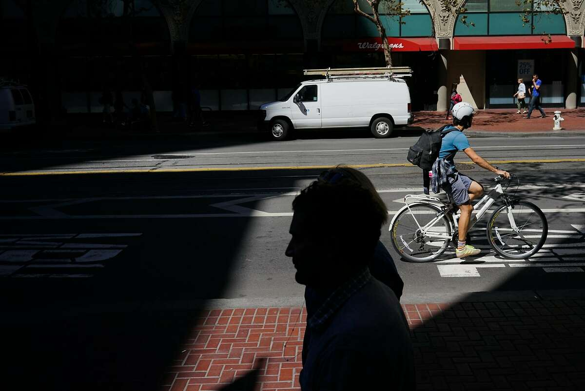 A cyclists rides down Market Street in San Francisco, Calif. on Friday, Sept. 25, 2015. Mayor Ed Lee said he will veto legislation that would require police to make cyclists who don't stop at stop signs a low priority.