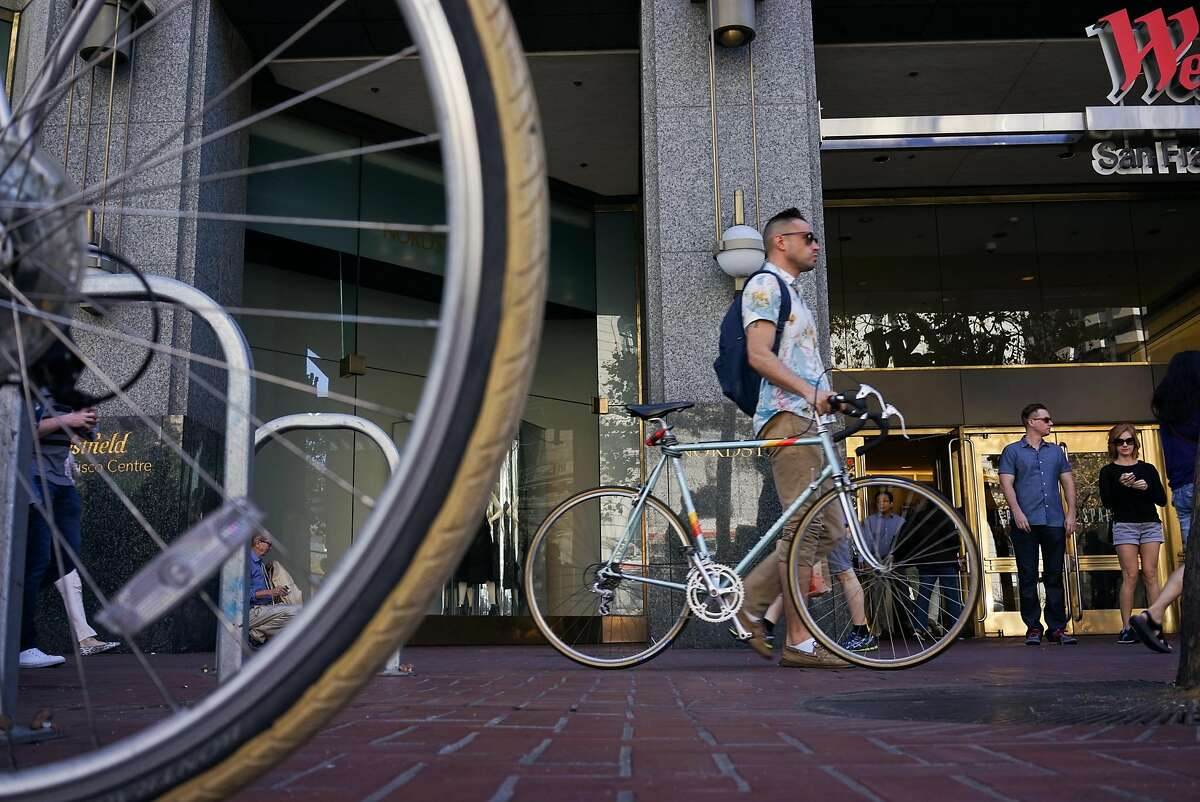 A man passes a locked up bike on Market Street in San Francisco, Calif. on Friday, Sept. 25, 2015. Mayor Ed Lee said he will veto legislation that would require police to make cyclists who don't stop at stop signs a low priority.