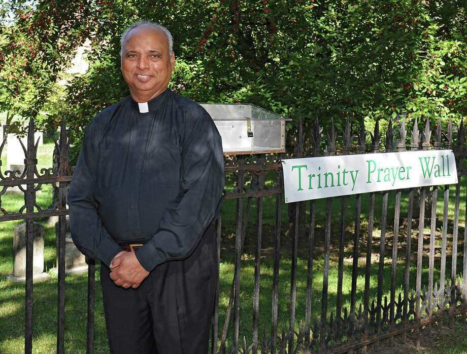 Rev. Desmond Francis, rector of Trinity Church Lansingburgh, stands next to the prayer box on the fence outside the church on Wednesday, Sept. 23, 2015 in Troy, N.Y. (Lori Van Buren / Times Union) Photo: Lori Van Buren / 00033469A
