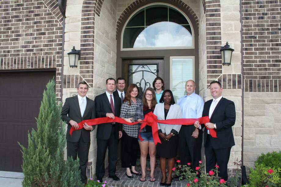 Representatives from Perry Homes join the Benefit Home buyers for a ribbon-cutting at their home in Bridgeland.