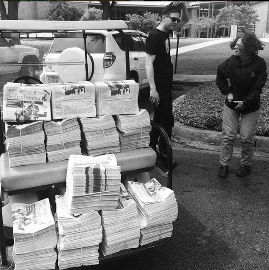 Luke Wise (left, next to cart), editor of the Trinitonian newspaper, will graduate next May. with copies of the Trinitonian at Trinity University) Photo: Courtesy Photo