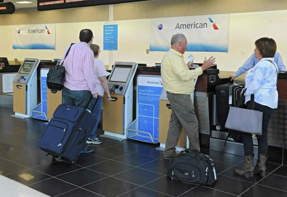 Temporary American Airlines banners are seen behind their ticket counter at Albany International Airport on Friday, Sept. 25, 2015 in Colonie, N.Y. The new permanent signs will probably be hung at night time. (Lori Van Buren / Times Union) Photo: Lori Van Buren / 10033500A