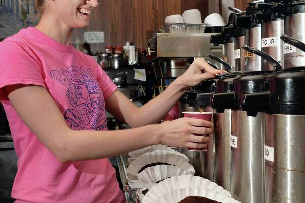 Javateer Amelia Beach pours a cup of the coffee of the day, pecan sticky bun, at Professor Java's coffee house Friday Sept. 25, 2015 in Colonie, NY.  (John Carl D'Annibale / Times Union)