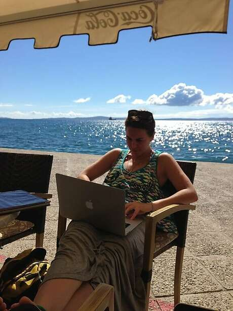 An Expensify employee works on her Macbook during the company's annual month-long getaway in 2013, when the firm took dozens of workers to the beaches of Croatia. Photo: Expensify
