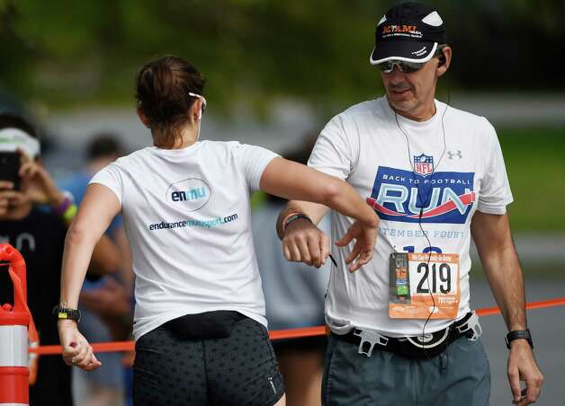 Kelly Roth, left, hands off to Chris Tzanakos during the Ragnar Relay Friday afternoon Sept. 25, 2015 in Saratoga Springs, N.Y.   (Skip Dickstein/Times Union) Photo: SKIP DICKSTEIN / 00033512A