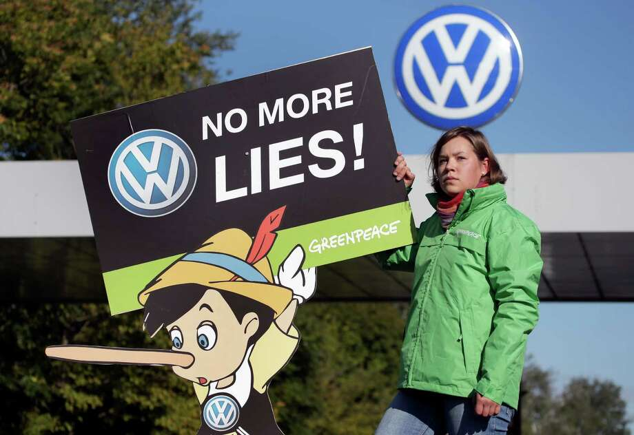 An activist of the environmental protection organization 'Greenpeace' holds a protest poster in front of a factory gate of the German car manufacturer Volkswagen in Wolfsburg, Germany, Friday, Sept. 25, 2015, where the supervisory board meet to discuss who to name as CEO after Martin Winterkorn quit the job this week over an emissions-rigging scandal that's rocking the world's top-selling automaker. (AP Photo/Michael Sohn) Photo: Michael Sohn, STF / AP