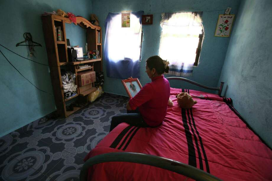 In this Aug. 8, 2015 photo, Afrodita Mondragon, mother of slain college student Julio Cesar Mondragon, looks at her son's portrait inside her son's bedroom, which she maintains as he left it and sometimes sleeps there, in San Miguel Tecomatlan, a rural town in the hills of Mexico state. Although international attention has been focused on the 43 students who vanished a year ago Saturday, six others died at the hands of police in those hours. Among them was Mondragon, a 22-year-old married father of a 2-year-old. In a report by a military unit at the scene, his face had been peeled off with a knife. (AP Photo/Marco Ugarte) Photo: Marco Ugarte, STR / Associated Press / AP