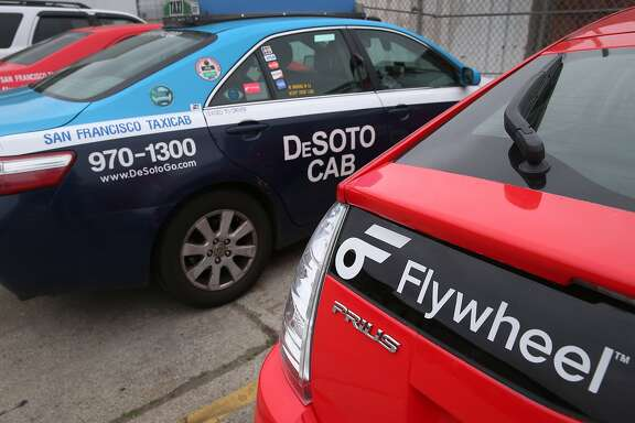 Flywheel taxis are being prepped to be put into service at the DeSoto maintenance yard in San Francisco, Calif. on Tuesday, Feb. 17, 2015. Flywheel has entered into an agreement with DeSoto to rebrand its fleet with the start-up company's taxi-hailing app logo.