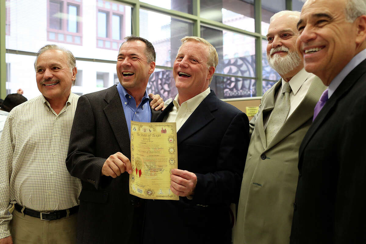 Vic Holmes, center/left, and Mark Phariss hold their marriage license, issued moments earlier, as they celebrate with Frank Stenger-Castro, one of their attorneys and a friend, from left, Bexar County Clerk Gerry Rickhoff and former Congressman Charlie Gonzalez at the Bexar County Marriage License Office in the Paul Elizondo Tower in San Antonio on Friday, Sept. 25, 2015.
