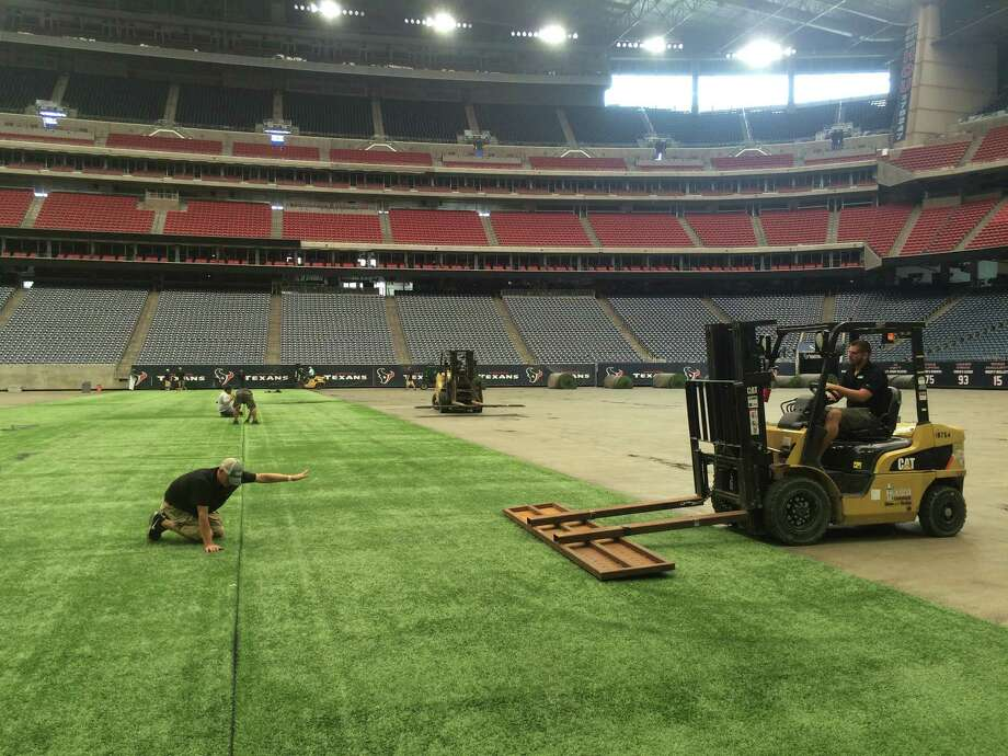 Workers labor to put the finishing touches on the installation of AstroTurf surface at NRG Stadium. The AstroTurf is replacing the Texans' previous grass surface for the rest of the season. Photo: Aaron Wilson