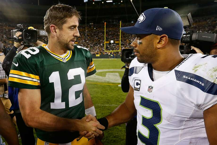 Russell Wilson (right) saw the hand of God at work in Seattle's victory in the NFL Championship Game, leading Aaron Rodgers (left) to note a reversal in Sunday's rematch. Photo: Christian Petersen, Getty Images