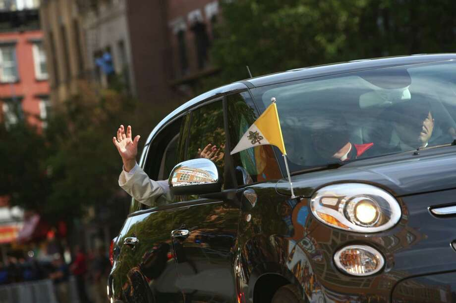 Pope Francis greets the crowd from his Fiat flying the Vatican flag as he arrives Friday at a school in New York's East Harlem neighborhood. Fiat hasn't enjoyed this level of visibility since its hiatus from the U.S. market ended four years ago. Photo: ERIC THAYER, STR / NYTNS