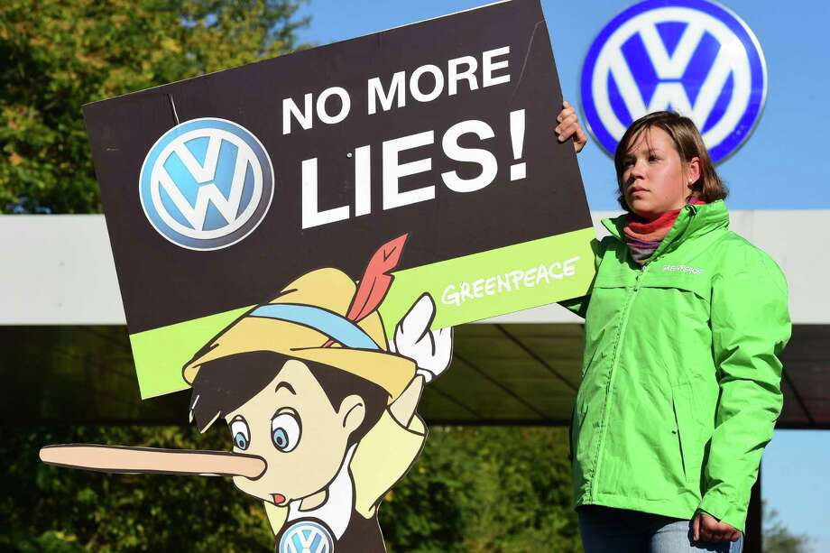 An activist makes a pointed request on Friday during a Greenpeace demonstration in front of Volkswagen's headquarters in Wolfsburg, Germany. Photo: JOHN MACDOUGALL, Staff / AFP