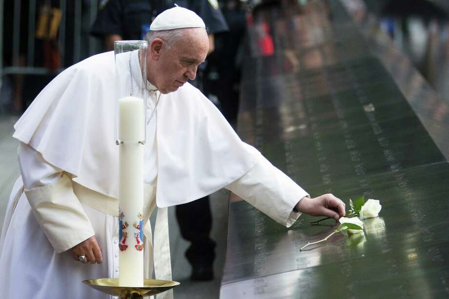 Pope Francis places a white rose at the South Pool of the 9/11 Memorial in New York on Friday. Photo: John Minchillo, STF / AP