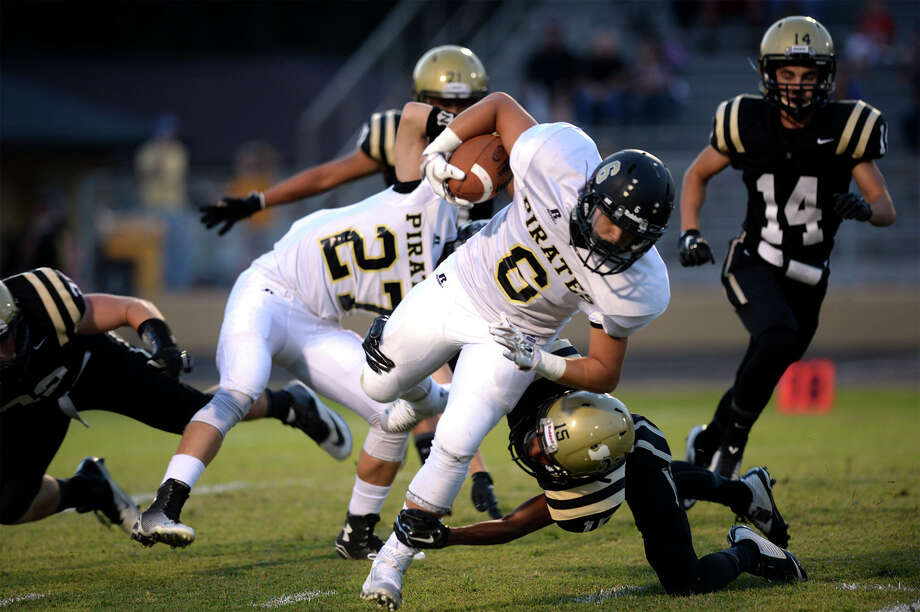 Vidor's Ty Stevenson is taken down by Jalen Cunningham at the Bulldog's stadium Friday night.   Photo taken Friday, September 25, 2015 Guiseppe Barranco/The Enterprise Photo: Guiseppe Barranco, Photo Editor