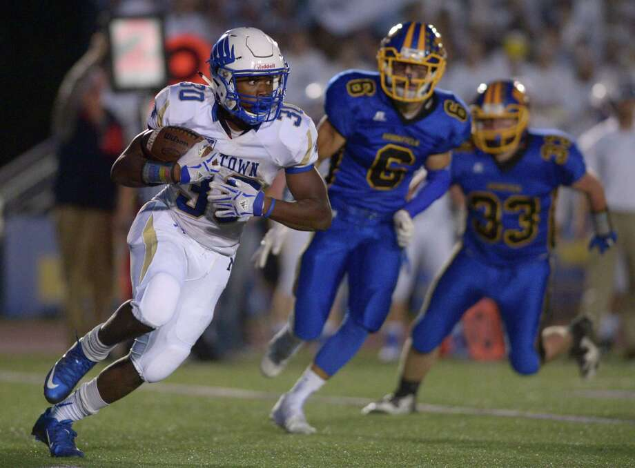 Newtown's Hunter Cobb (30) is chased by Brookfield's Nick Seis (6) as he sweeps around the corner in the high school football game between Newtown and Brookfield high schools, on Friday night, September 25, 2015, at Brookfield High School, Brookfield, Conn. Photo: H John Voorhees III / Hearst Connecticut Media / The News-Times