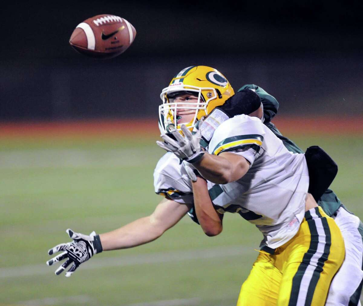 Trinity receiver Dominick Svrcek (#5) attempts to make a recpetion while being draped by a Norwalk defender during the high school football game between Norwalk High School and Trinity Catholic High School at Norwalk, Conn., Friday night, Sept. 25, 2015. Svrcek did not make the catch on the play.