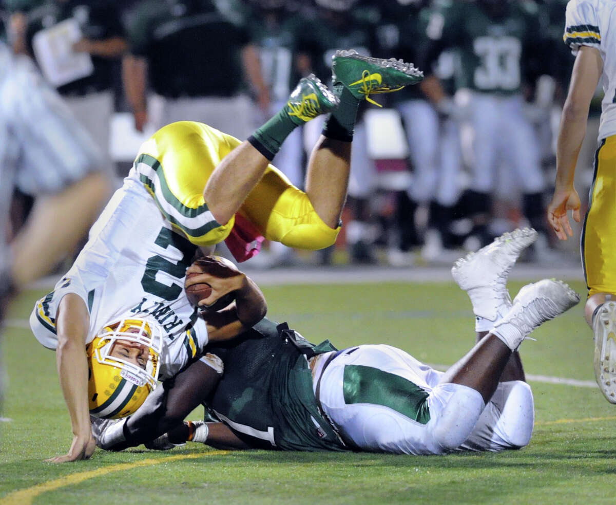 At left, Trinity quarterback Anthony Lombardi gets flipped as he is sacked by Norwalk's Anthony Wooten (#71) during the high school football game between Norwalk High School and Trinity Catholic High School at Norwalk, Conn., Friday night, Sept. 25, 2015.