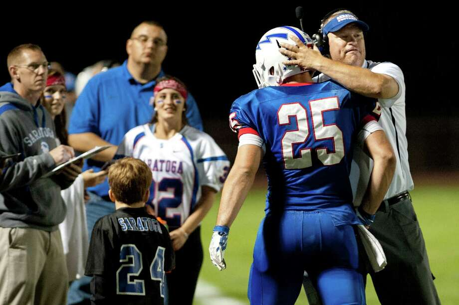 Saratoga's coach Terry Jones, right, celebrates a touchdown with Dakota Harvey, second from right, during their football game against Shenendehowa on Friday, Sept. 25, 2015, at Saratoga Springs High in Saratoga Springs, N.Y. (Cindy Schultz / Times Union) Photo: Cindy Schultz / 10033490A