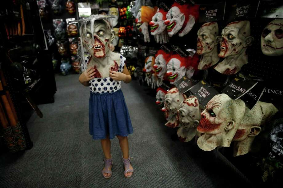 "In this Sept. 2, 2015 photo, six-year-old Olivia Vlaicu, of Maywood, N.J., tries on an ""ancient zombie"" mask at the Spirit Halloween store, in Paramus, N.J. Spirit Halloween, a chain of more than 1,150 pop-up shops across the country, has reincarnated a former Staples store and filled it with 4,000 costumes and accessories with themes ranging from zombies to superheroes and princesses to prison inmates. (AP Photo/Mel Evans) Photo: Mel Evans, STF / AP"