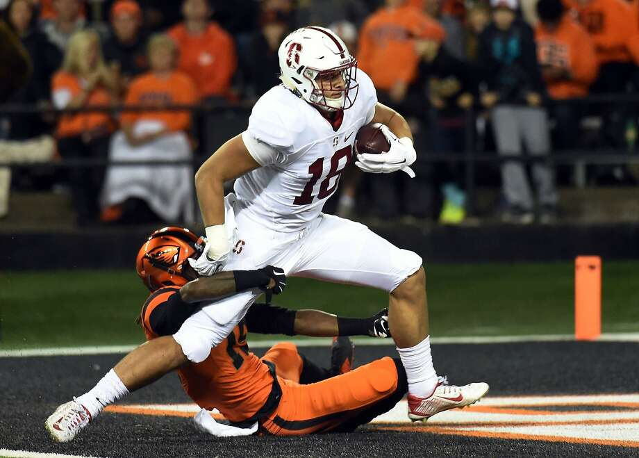 With Oregon State cornerback Larry Scott holding on, Stanford tight end Austin Hooper scores on a 42-yard pass play. Photo: Steve Dykes, Getty Images