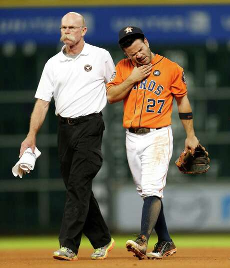 Assisted by trainer Rex Jones, second baseman Jose Altuve leaves the field in pain after colliding with Astros teammate Carlos Correa while chasing a seventh-inning fly ball into shallow center field Friday night at Minute Maid Park. Photo: Karen Warren, Staff / © 2015 Houston Chronicle